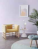 Designer chair, side table and stool in the room with a lilac wall