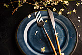 Place setting with peach blossom branch and blue plate