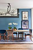 Magnolienleuchte über Esstisch mit Orchideen, Kunstwerke an blauer Wand