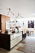 Blick auf Kücheninsel, dahinter lEssbereich in offenem Wohnraum