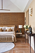 Console table and double bed in bedroom with bamboo wall