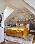 Yellow quilt on double bed in attic bedroom