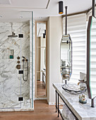 Marble shower cubicle, vintage mirrors and glass sink