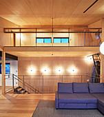 Elegant, double-height, wood-panelled living area in architect-designed house