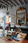 Antique mirror on blue wall and breakfast on table in dining room