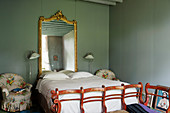 Antique bench at foot of bed below gilt-framed mirror in bedroom