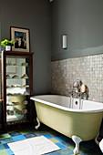 Pale green, free-standing bathtub against mosaic wall tiles in grey bathroom