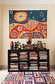 Mexikanischer Wandbehang über Bücherregal mit kunsthandwerklicher Vasensammlung