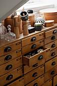 Schachteln, Flakons und Schaufensterpuppenhände auf antikem Kurzwarenschrank