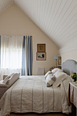 Linen scatter cushions and bed spread on double bed in bedroom