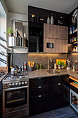 Gas cooker and black glossy cabinets in small masculine kitchen