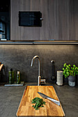 Chopped herbs on wooden chopping board in grey kitchen