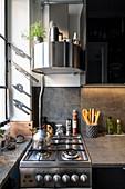 Runde Dunstabzugshaube überm Gasherd in kleiner Küche in Grau