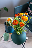 Orange ranunculus in petrol-blue vase