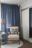 Classic armchair in front of blue curtain in bedroom