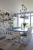 High chair at table in open-plan dining room with floral wallpaper