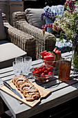 Pastries and fruit on table on sunny terrace