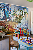Dragons on mural wallpaper and round tables in playroom