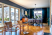 Classic chairs and dining area in open-plan interior with blue walls