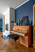Piano and piano stool in open-plan interior with blue wall