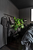 Clothes rail in bedroom with black walls
