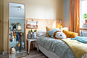 Free-standing mirror next to stool used as bedside table and bed in child's bedroom