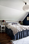 Bed with valance below sloping bedroom ceiling