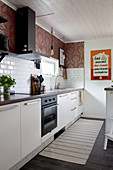 Subway tiles and vintage-style wallpaper in kitchen