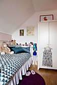 Metal bed with valance in child's bedroom with sloping ceiling