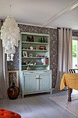 Mint-green shabby-chic dresser in open-plan interior