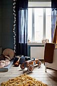 Wooden ride-on car in child's bedroom in shades of blue
