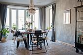 Esszimmer mit verschiedenen Stühlen, Kronleuchter und Ziegelboden
