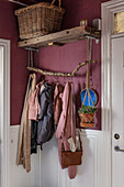 Plant hanger suspended from DIY coat rack on pink wal