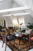 Antique chairs, sofa and side tables in lavishly decorated attic interior