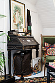 Black, antique bureau with inlay work next to green velvet armchair