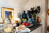Kitchen counter lavishly decorated with carafes, statues, oil lamps and picture