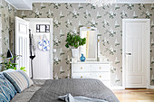 Double bed, white doors and lilac-patterned wallpaper in bedroom