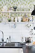 Crockery on kitchen shelves against floral wallpaper