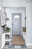 Coat rack and grey door in bright foyer