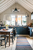 Blue cabinets and open roof structure in rustic kitchen-dining room