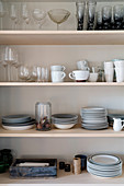 Glasses, cups and stacked plates on shelves