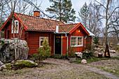 Rotes Schwedenhaus in rustikaler Winterlandschaft mit Felsen