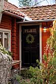 Schwarze Tür mit Kranz im winterlichen roten Schwedenhaus
