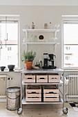 Rollwagen mit Holzkisten zwischen Fenstern in heller Küche
