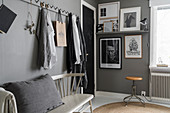 Row of pegs above spoke-back bench in grey bedroom
