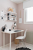 Shell chair at desk in child's bedroom in pink and white