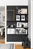 Pictures and books on ledges on black living room wall