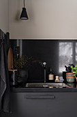 Sink in kitchen with dark grey cupboards and black splashback
