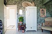 Oriental parasol on cupboard in bedroom with vintage-style wallpaper