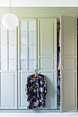 Floral kimono hanging from handle of wardrobe with panelled doors